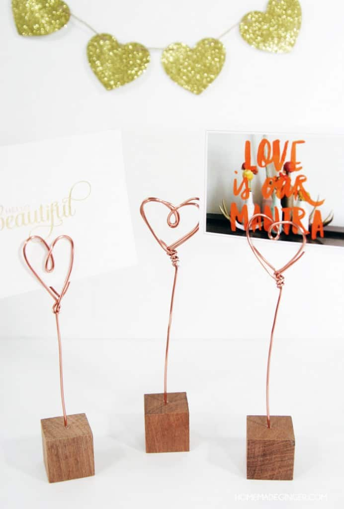 These little wire photo holders couldn't be easier to make. I saw some gold ones similar to these in different geometric shapes as I was browsing through a store a few months ago and decided to see how easy it was to make some heart versions! I also am loving all things copper right now and thought that using copper wire would send these over the edge of cuteness. I couldn't believe how easy they were to make and I LOVE how they turned out!!</p> <!-- /wp:paragraph -->  <!-- wp:paragraph --> <p><strong>It's simple to make wire photo holders at home. All you need is some copper wire, wooden blocks and a handful of other supplies to create DIY photo holders for your home.