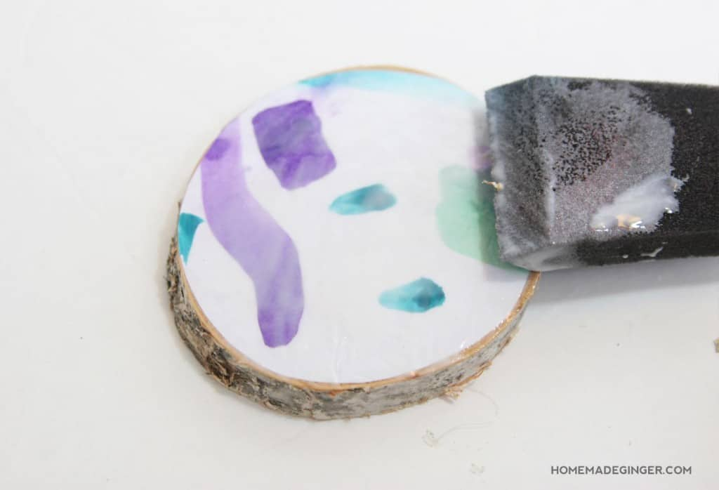 Turn kids art into adorable wood slice coasters! These DIY coasters couldn't be easier to make and look adorable displayed on the coffee table!